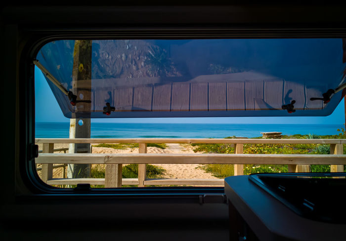 Ocean view through the window of a campervan Window Glass - Material Mode Of Transportation Transportation Water Nature Transparent Vehicle Interior No People Reflection Indoors  Sea Scenics - Nature Day Mountain Travel Sky Motion Swimming Pool Luxury Campervan Ocean