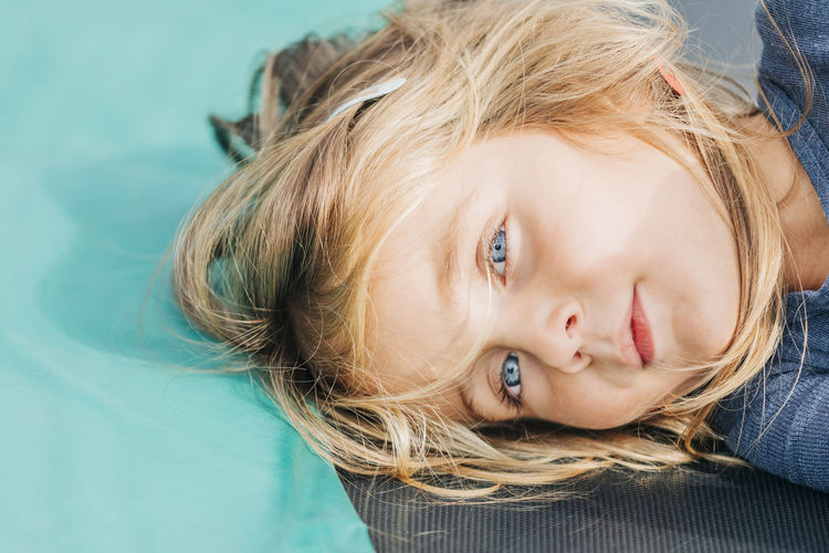 Close-up portrait of a girl lying down on floor