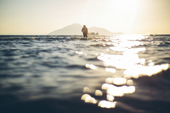 Time doesn't wait for no one Beauty In Nature Bokeh Horizon Over Water Idyllic Leisure Activity Lifestyles Nature Outdoors Reflection Rippled Scenics Sea Shore Silhouette Sky Sun Sunbeam Sunlight Sunset Tranquil Scene Tranquility Unrecognizable Person Vacations Water
