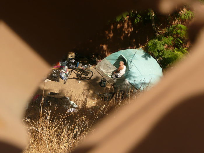 a blue tent from a homeless encampment behind Pinehurst neighborhood in San Jose, California, October 2017 Camping Blue Bum Close-up Day Focus On Background Fringe Grass Hidden Homeless Homelessness  Makeshift Makeshift Home Nature One Person Outdoors People Poor People  Poverty Selective Focus Tent Tents Transient Urban Campers Vagrancy