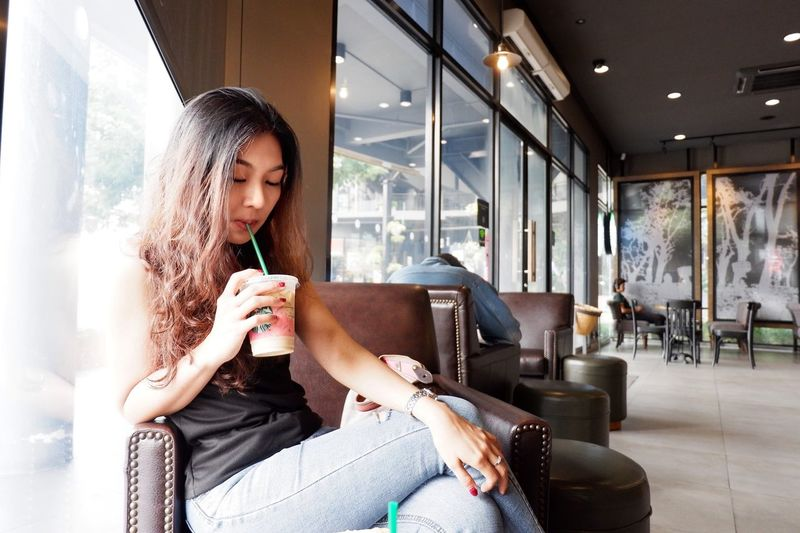 thai girl 134112 Sitting One Person Lifestyles Real People Leisure Activity Women Indoors  Young Women Day Casual Clothing Relaxation Food And Drink Window Adult Young Adult Drink Three Quarter Length Holding Drinking Hairstyle
