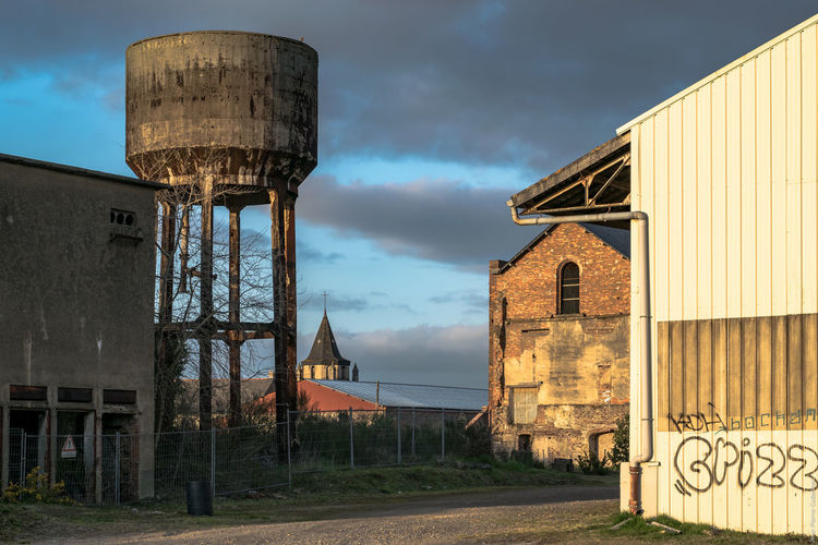 Water Tower And Houses Against Cloudy Sky