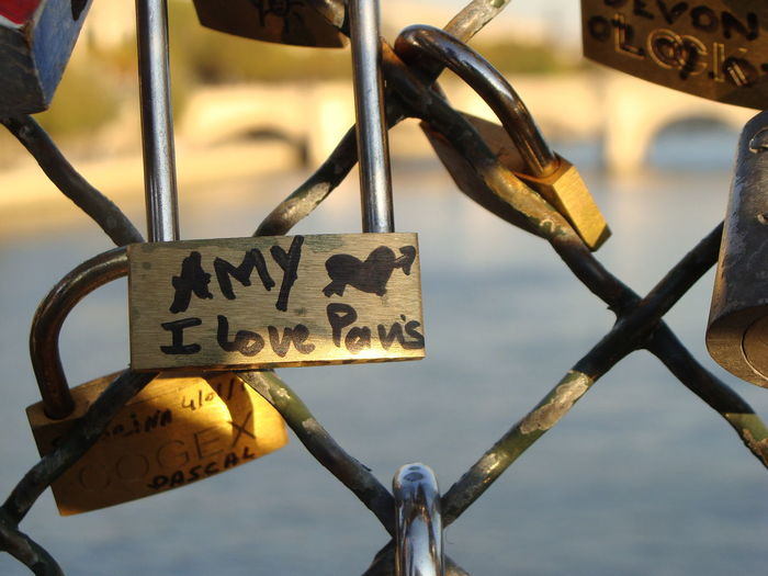 Close-up of padlocks and text on chainlink fence