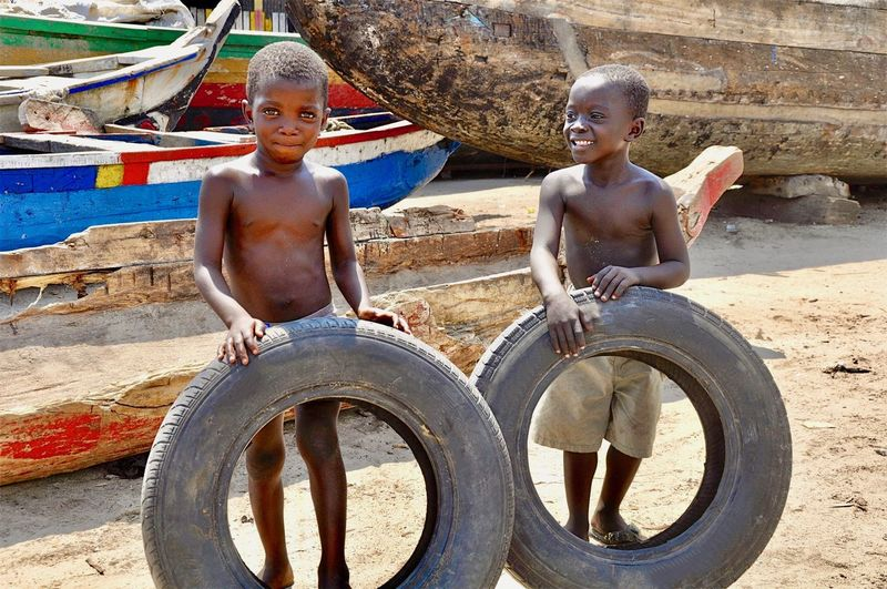 Portrait of smiling boys with tires at beach