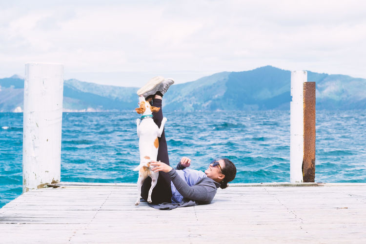 Side view of woman playing with her dog on a pier with blue sea and sky in background