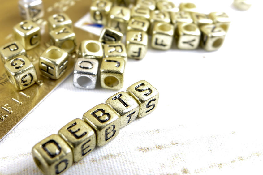 DEBT CONCEPT WITH GOLD DICE ON A WOODEN TABLE Arts Culture And Entertainment Close-up Communication Credit Card Debt Crisis Dice Gambling Game Of Chance High Angle View Indoors  Leisure Activity Leisure Games Luck Metal No People Number Opportunity Relaxation Still Life Table Text Wealth Western Script
