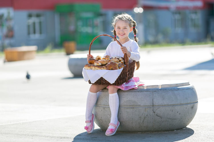 Full length of smiling girl holding basket with food while sitting on road