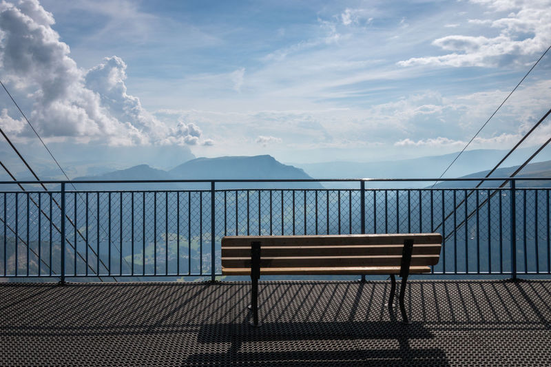 Empty bench by railing against sky