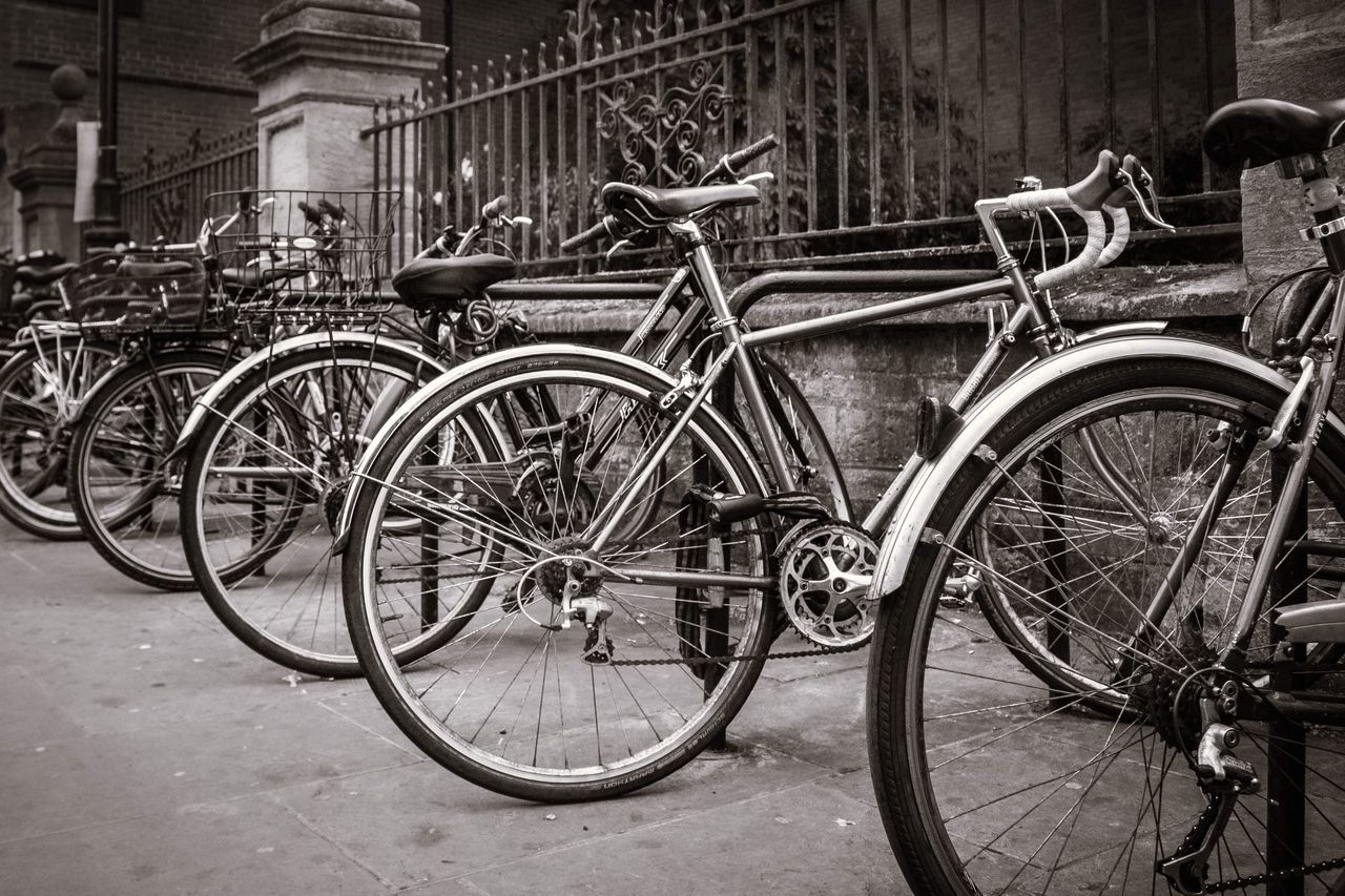 transportation, mode of transportation, land vehicle, bicycle, city, stationary, day, no people, architecture, street, metal, focus on foreground, outdoors, footpath, parking, travel, wheel, sidewalk, railing, built structure, spoke