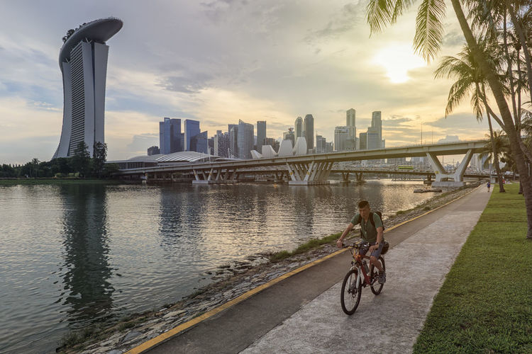 Singapore, Singapore - October 17, 2018: Woman cycling in down town in front of the Marina Bay Sands and Modern Art Museum at sunset Singapore Marina Bay Sands Merlion Haji Lane, Singapore Arab Street Cityscape Modern Art Museum Buddah Tooth Relic Temple