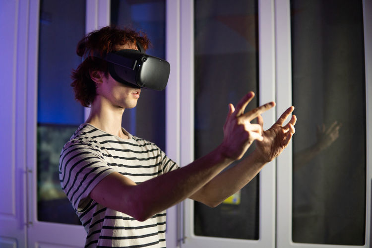 Young man wearing virtual reality simulator playing game at home