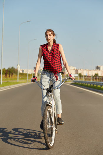 Portrait of young woman riding bicycle on road