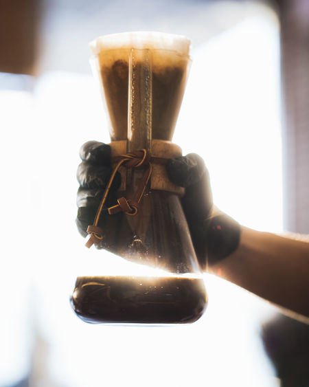 Black Coffee inside Lab Glass in Hand Ijas Muhammed Photography Human Hand Hand Holding Human Body Part One Person Focus On Foreground Real People Food And Drink Close-up Day Sunlight Unrecognizable Person Drink Lifestyles Refreshment Leisure Activity Container Indoors  Coffee Glass Finger