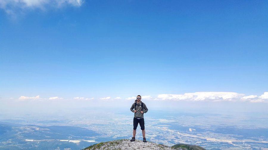Full length of hiker standing on mountain against blue sky