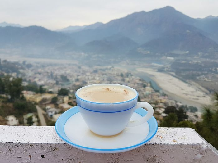 Close-up of coffee cup on railing against mountains