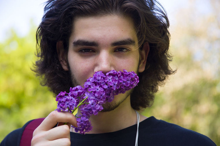 Beauty In Nature Boy Close-up Flower Headshot Holding Lilac Lilac Flower Man Nature Outdoors Portrait Purple Showcase April Young Man Young Men Telling Stories Differently Uniqueness