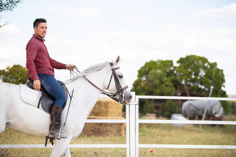 Mid adult man riding horse against sky