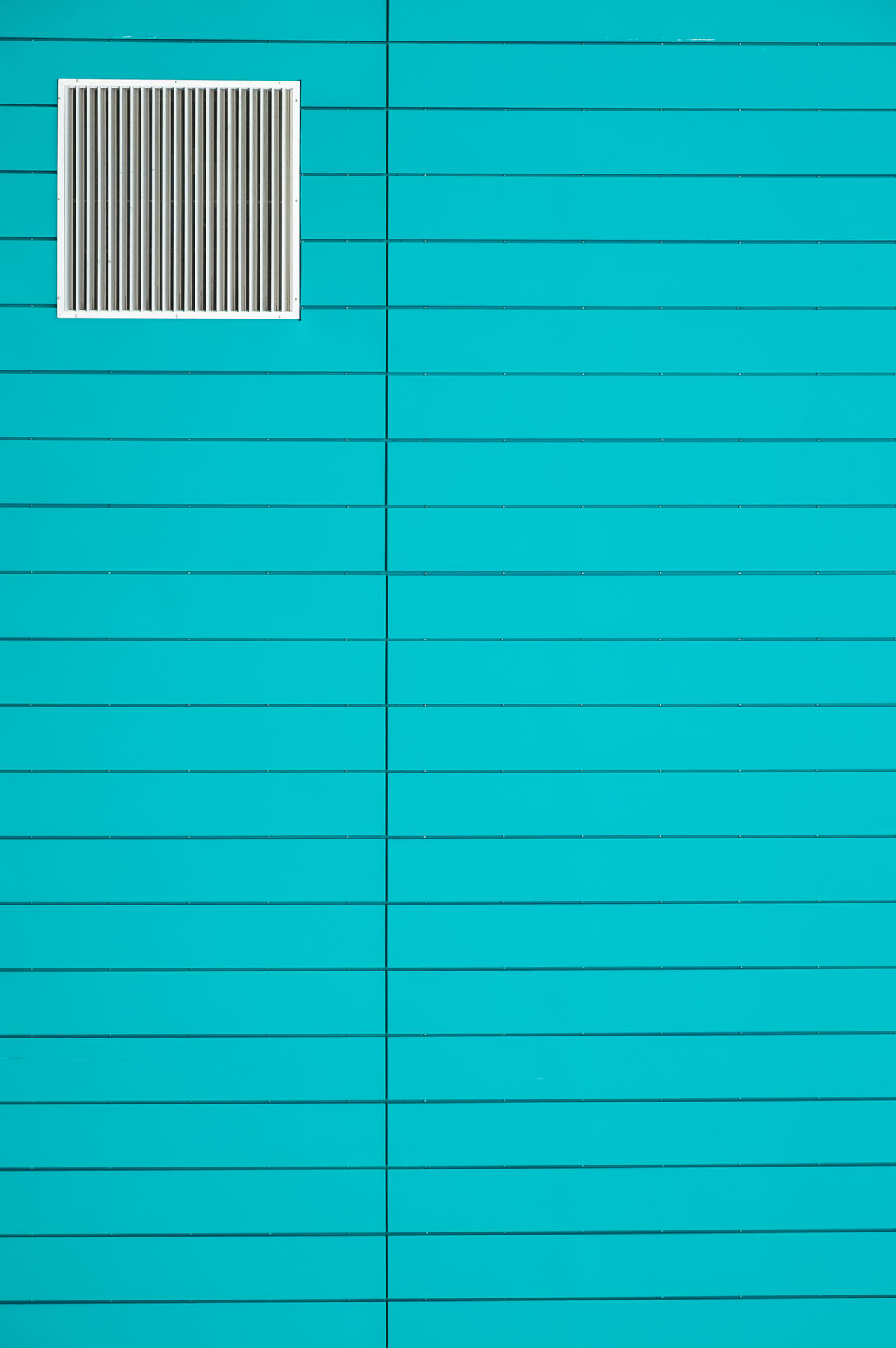 Window on turquoise wall