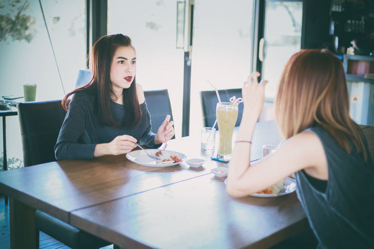 Friends Talking While Having Meal In Restaurant