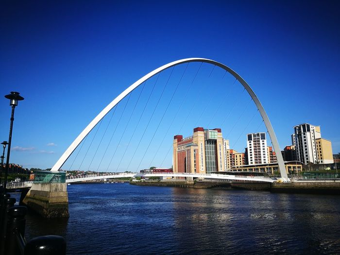 Bridge Over River By City Against Clear Blue Sky