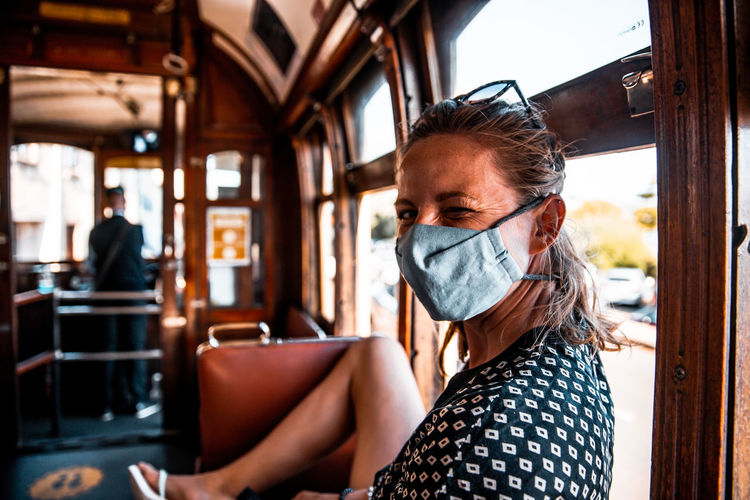 Female wearing mouth and nose mask in public transportation covid-19 regulations