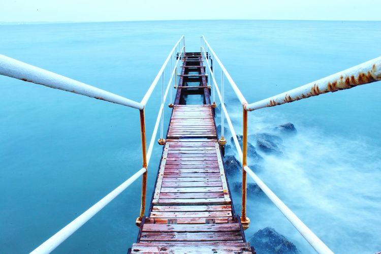 High angle view of steps on footbridge over sea