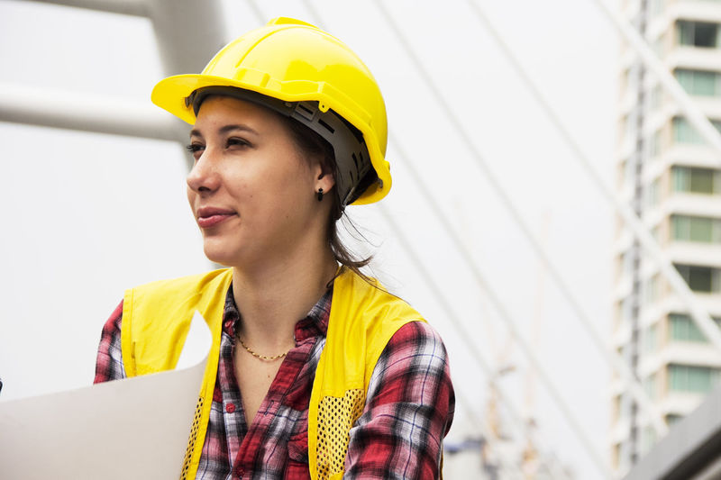 Mid adult woman looking away at construction site