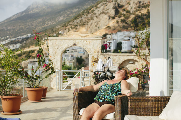Midsection of woman sitting by potted plants on mountain