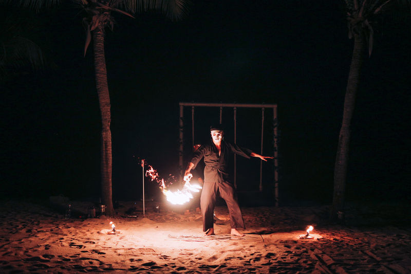 Woman standing against illuminated fire at night