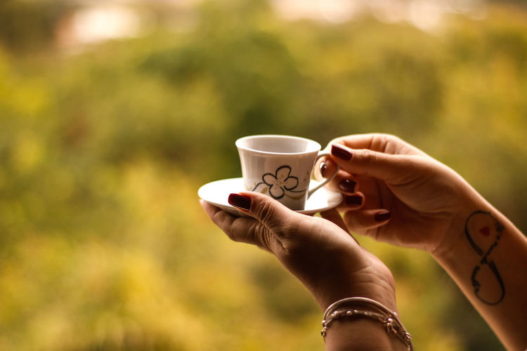 Drinking coffee with nature's tranquility. Human Hand Drink Women Holding Coffee - Drink Coffee Cup Drinking Tea - Hot Drink Close-up
