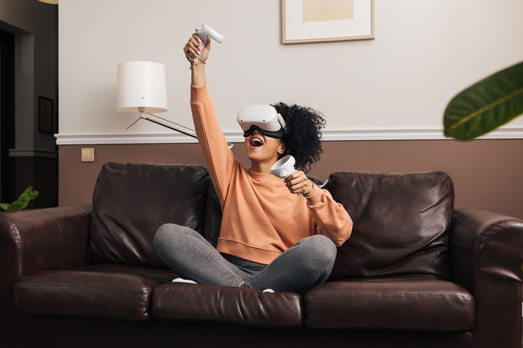 Laughing woman playing video game while sitting on sofa at home