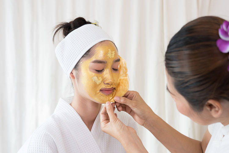 Massage therapist removing facial mask from young woman face