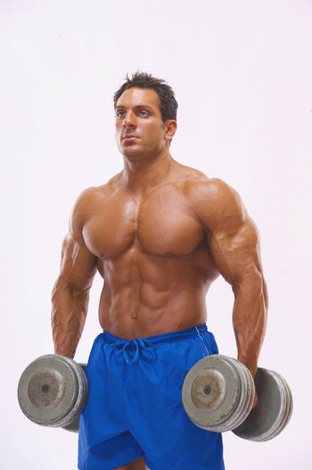 Man looking away while standing with dumbbell against white background
