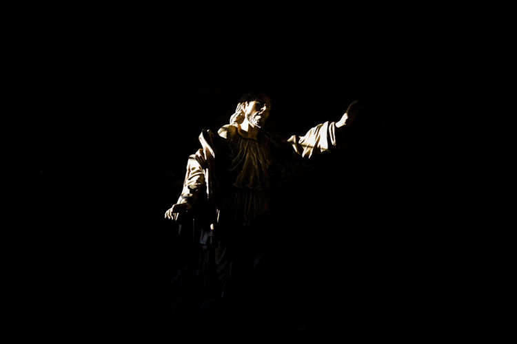 Statue against black sky at night