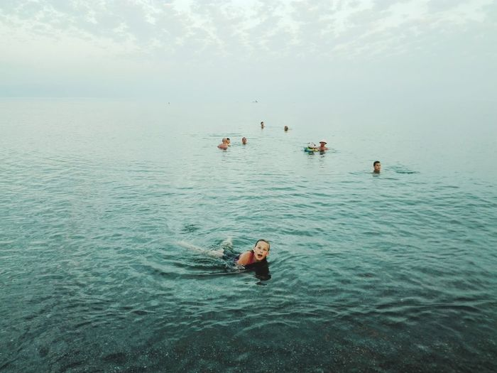 High Angle View Of People Swimming In Sea Against Sky
