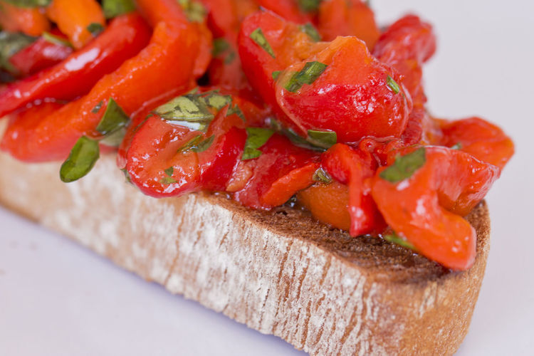 Close up of a slice of bruschetta with red sweet filleted peppers.