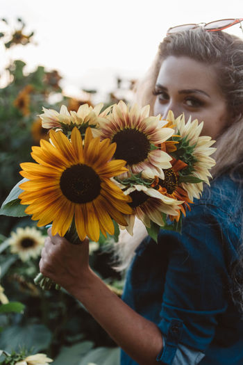 Young woman with sunflowers on yellow flowering plant