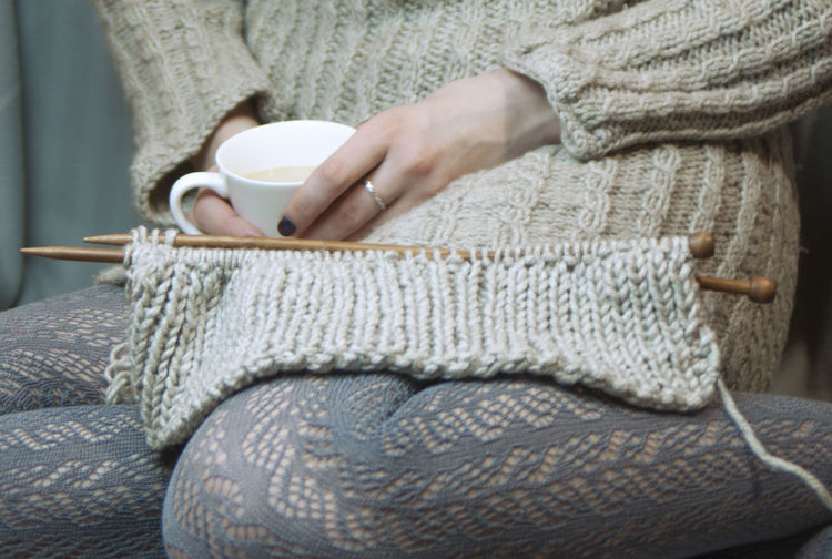 a young woman knits on the spokes and drinks coffee Ajurno Knitting Needles Ajurno Weaving Lace Cozy Hands Home Knitted Sweater Openwork Woman Coffee Time Copy Space Craft Gray Hand Holding Hot Drink Human Hand Keep Warm Lace Openwork Textile Wool