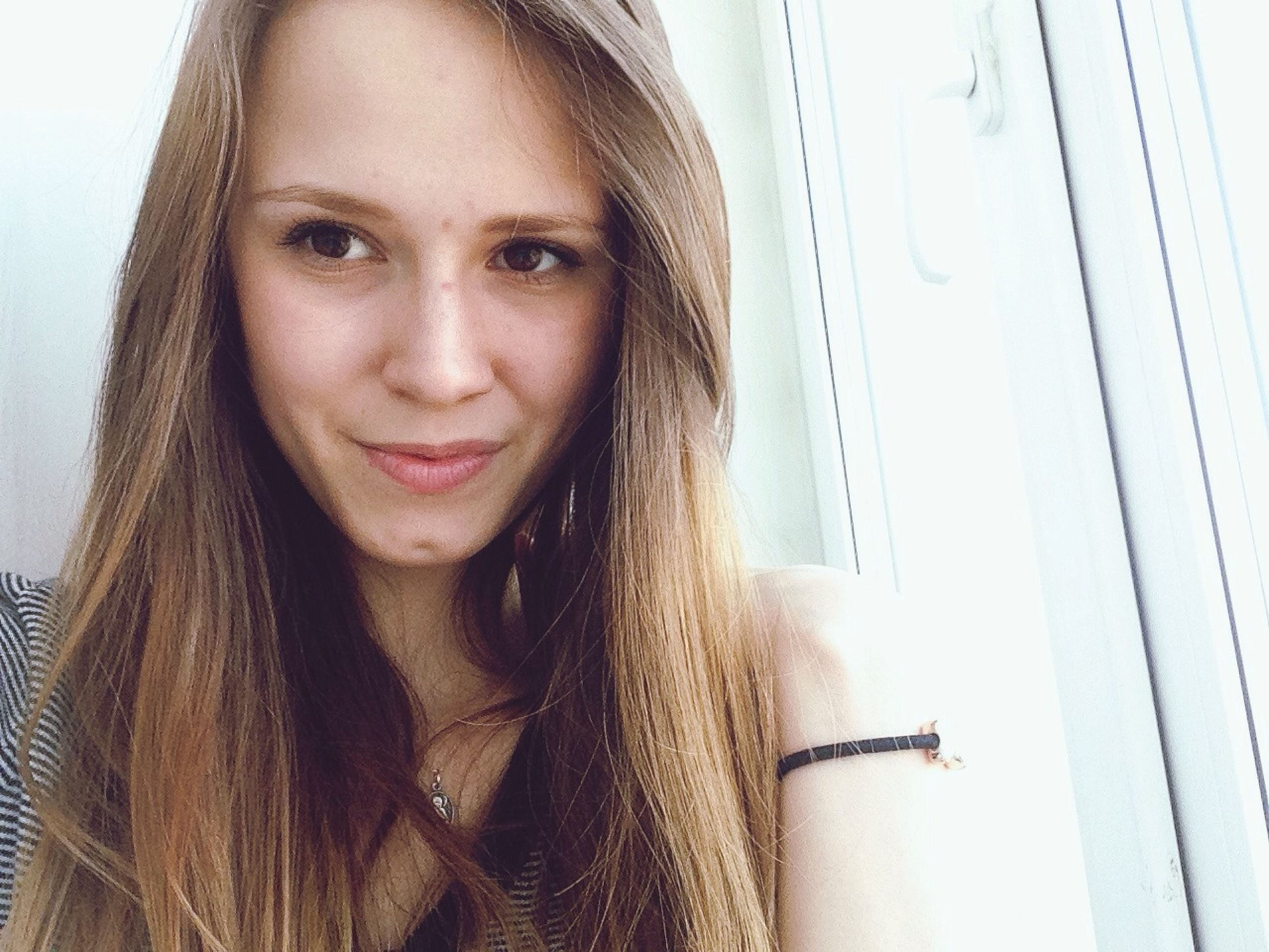 young women, young adult, long hair, person, lifestyles, looking at camera, portrait, indoors, front view, headshot, leisure activity, smiling, beauty, brown hair, black hair, femininity, casual clothing