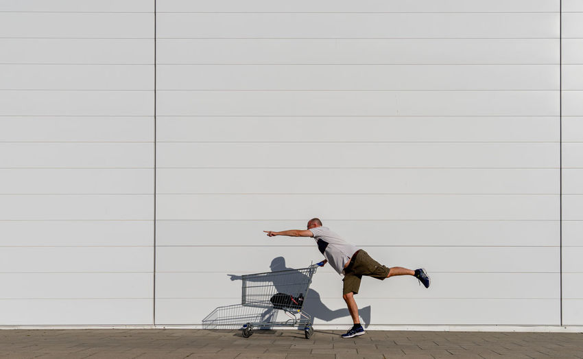 Side view of man with shopping cart standing against wall