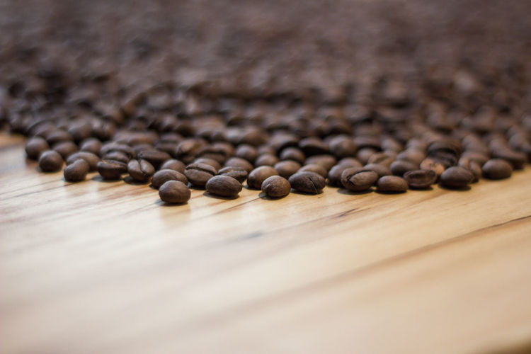 Coffee - Drink Food And Drink Coffee Roasted Coffee Bean Selective Focus Brown Large Group Of Objects Food Close-up No People Caffeine Indoors  Still Life Table Wood - Material Freshness Roasted Drink Spilling Abundance Textured Effect