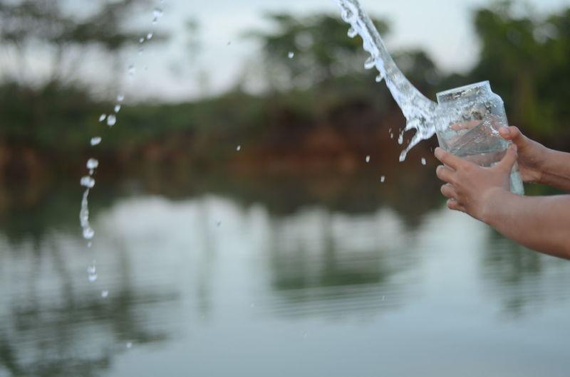 Cropped hands splashing water from jar by lake