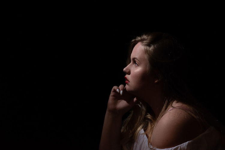 Side view of thoughtful woman looking away against black background