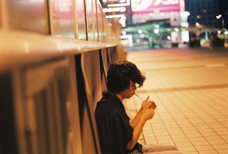 Side view of man smoking while sitting on footpath