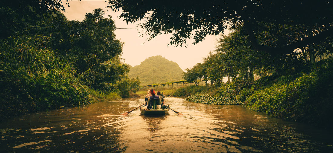 Rear View Of People Sitting On Boat In River Against Trees
