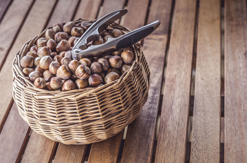 High angle view of hazelnuts and nutcutter in wicker basket on table