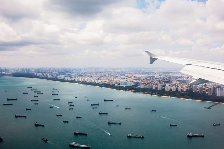 Aerial view of sea and cityscape against sky