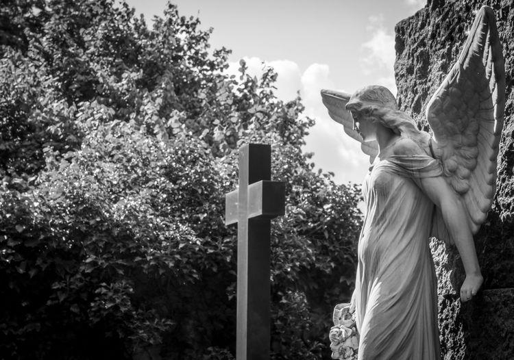 Low Angle View Of Angel Statue In Cemetery Against Sky