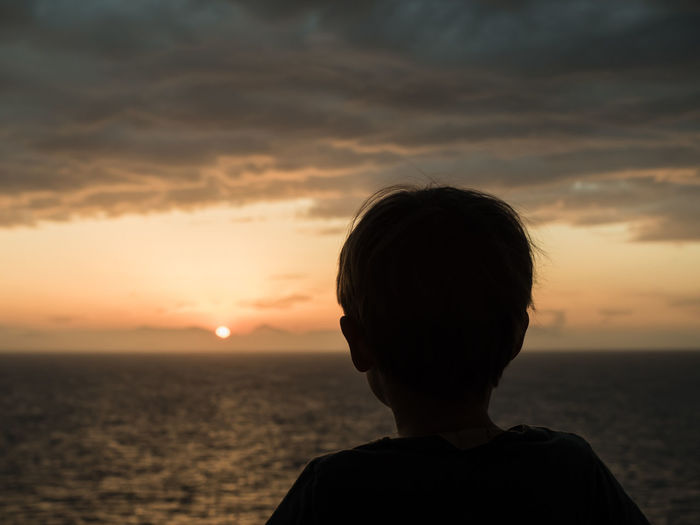 Rear view of a boy overlooking calm sea at sunset