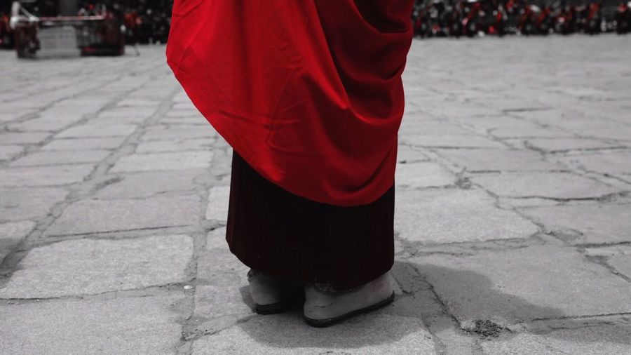 Low section of buddhist monk standing on footpath